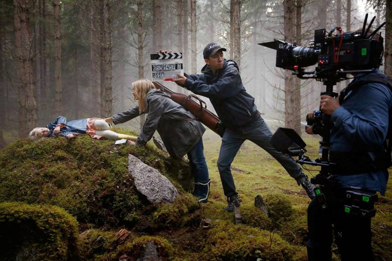 From the set of the movie Jordskott. A child actress is lying on a stone covered in green moos, interacting with a crew member. A clip board is held up to the cameraman, standing on the far right, ready to shoot.